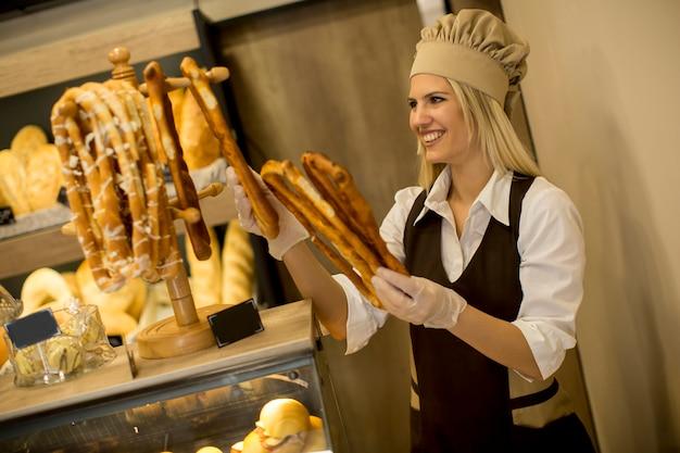 Recht junge frau, die brot in der bäckerei verkauft