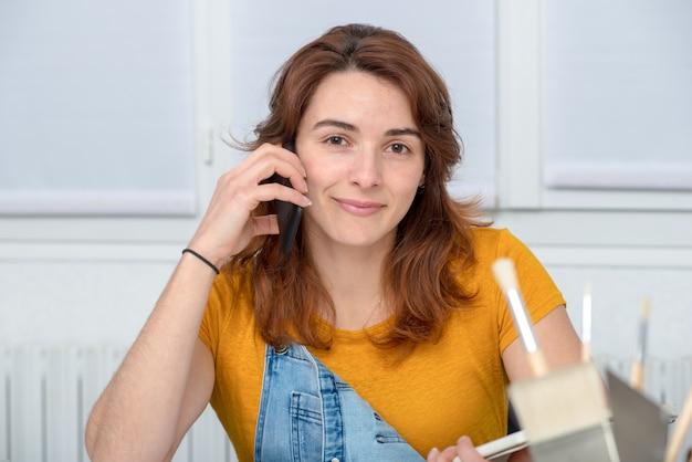 Recht junge frau, die diy spricht am telefon tut