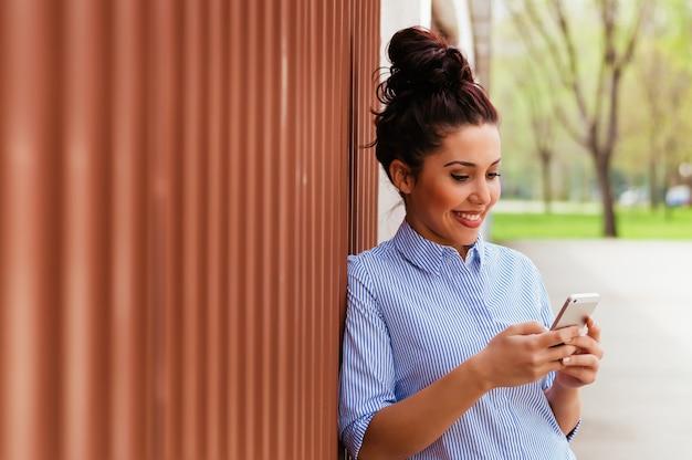 Recht junge frau, die draußen smartphone verwendet