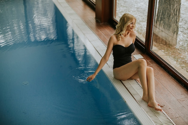 Recht junge frau, die durch den swimmingpool relaing ist