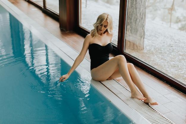 Recht junge frau, die durch den swimmingpool sitzt