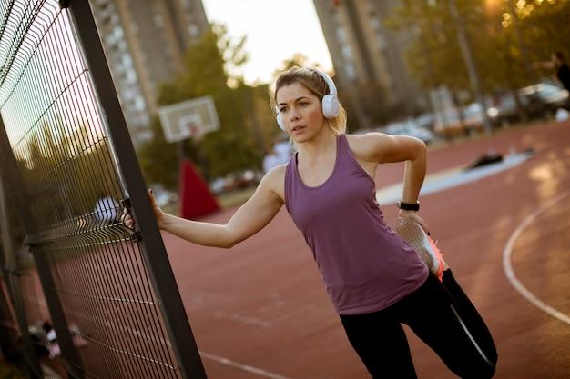 Recht junge frau, die während des sporttrainings ausdehnt