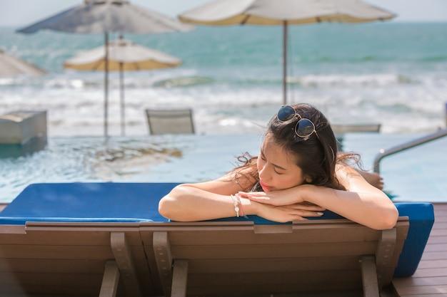 Recht junge frau entspannen sich, lügenstrand-klubsessel, sommerferien-feiertagskonzept