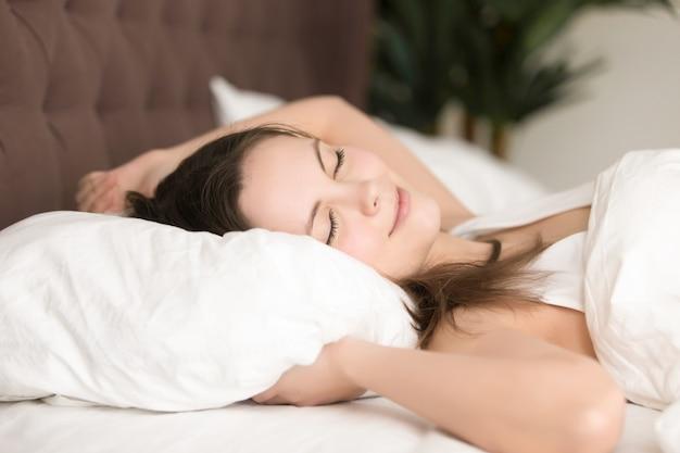 Recht junge frau genießt langen schlaf im bett