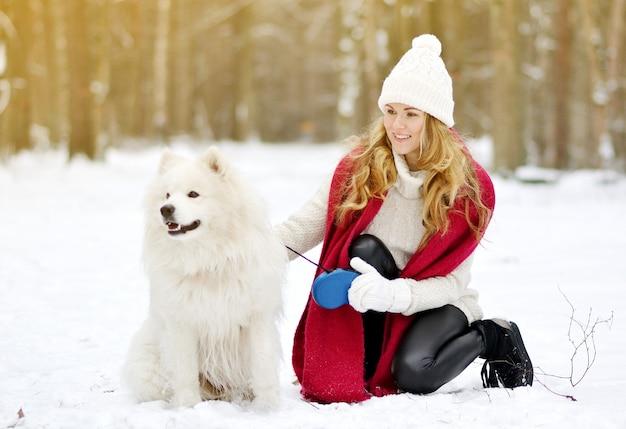 Recht junge frau im verschneiten winter forest park walking playing mit ihrem hundeweißen samoyed seasonal