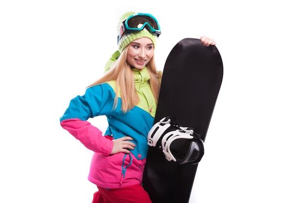 Recht junge frau in der skiausstattung und in den skibrillen halten snowboard