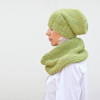 Recht junge frau in der warmen grünen strickmütze und im snood