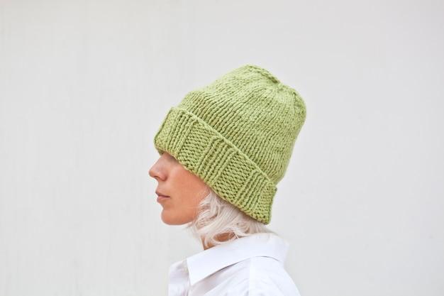 Recht junge frau in der warmen grünen strickmütze