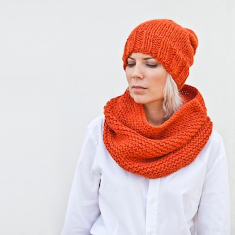 Recht junge frau in der warmen orange strickmütze und im snood