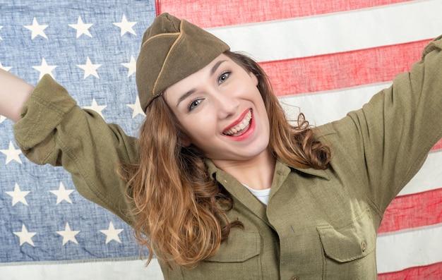 Recht junge frau in wwii-uniform wir mit amerikanischer flagge