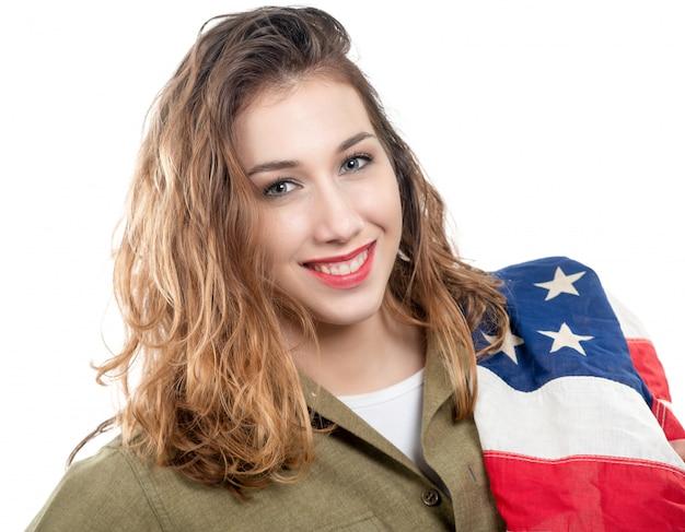 Recht junge frau in wwii-uniform wir mit einer amerikanischen flagge auf weiß