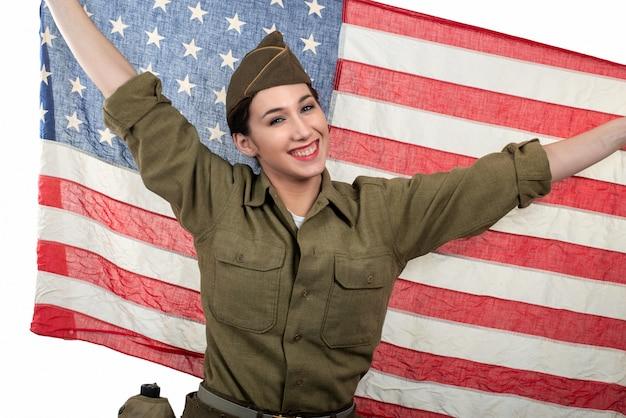 Recht junge frau in wwii-uniform wir mit einer amerikanischen flagge