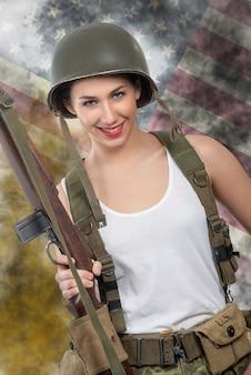 Recht junge frau kleidete in der wwii-militäruniform mit sturzhelm und gewehr an