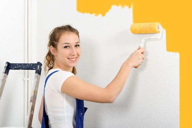 Recht junge frau malt die wand auf orange