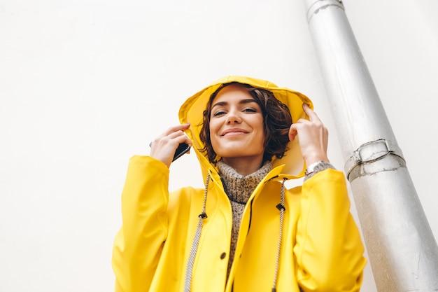 Recht junge frau mit dem gelockten braunen haar, das gelben mantel wegen des schlechten wetters draußen steht vor weißer wand trägt