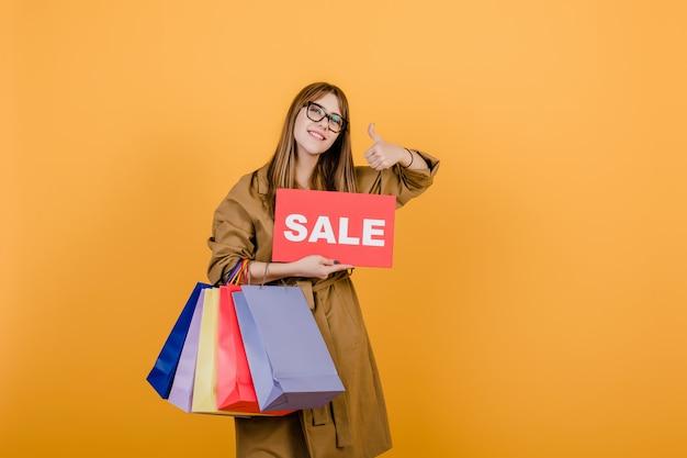 Recht junge frau mit dem verkaufszeichen und bunten einkaufenbeuteln getrennt über gelb