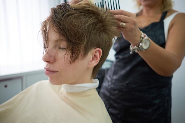 Recht junge frau mit den geschlossenen augen, die am friseursalon sich entspannen. friseurumhüllungskunde am friseursalon oder am schönheitssalon.
