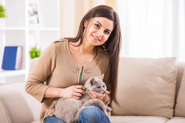 Recht junge frau mit ihrer katze auf der couch zu hause.