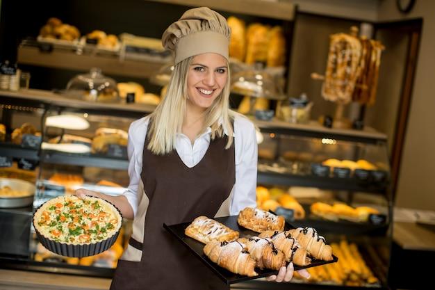 Recht junge frau mit quiche lorraine in der bäckerei