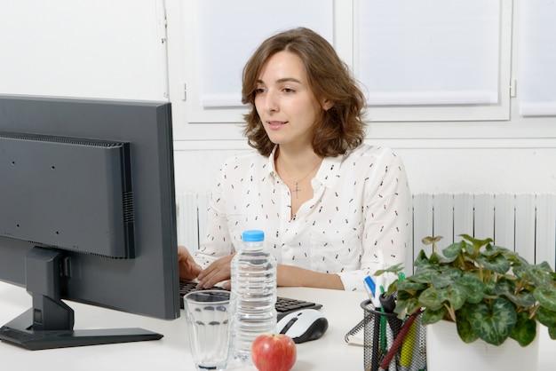Recht junge geschäftsfrau, die am pc im büro arbeitet