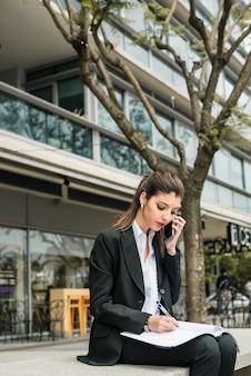 Recht junge geschäftsfrau, die am telefon beim schreiben über ordner an draußen spricht