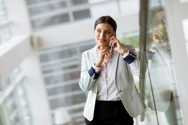 Recht junge geschäftsfrau steht auf der treppe im büro und benutzt handy