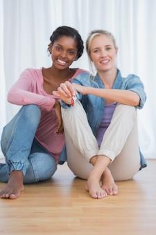 Recht junge housemates, die ihre neuen hausschlüssel zeigen