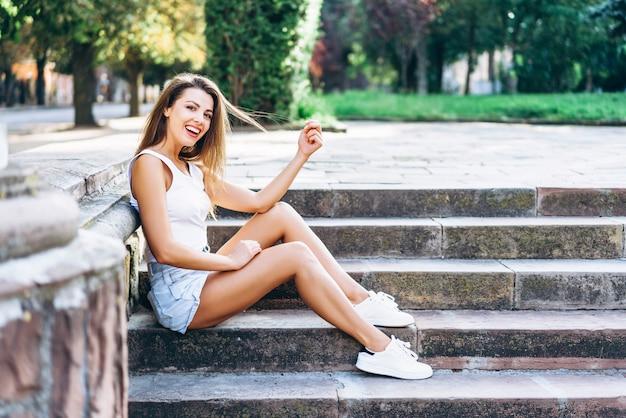 Recht junge lächelnde brunettemädchenentspannung im freien auf der straße.