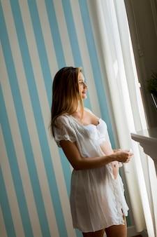 Recht junge schwangere frau, welche die blaue abgestreifte wand im raum bereitsteht