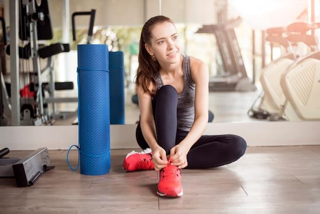 Recht junge sportfrau bindet ihre turnschuhe in der turnhalle, gesunder lebensstil