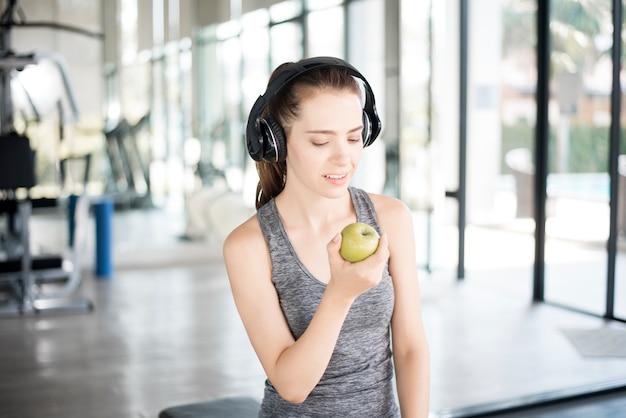 Recht junge sportfrau in der turnhalle mit grünem apfel, gesunder lebensstil