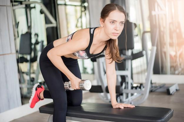 Recht junge sportfrau ist training in der turnhalle, gesunder lebensstil