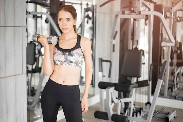 Recht junge sportfrau ist training in der turnhalle