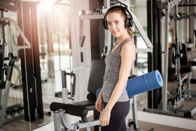 Recht junge sportfrau ist training mit matte in der turnhalle, gesunder lebensstil