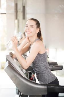 Recht junge sportfrau ist trinkwasser auf tretmühle in der turnhalle, gesunder lebensstil