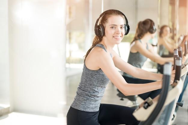 Recht junge sportfrau ist übung auf fahrrad in der turnhalle