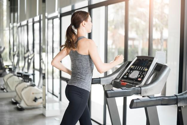 Recht junge sportfrau läuft auf tretmühle in der turnhalle, gesunder lebensstil