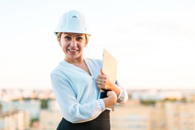 Recht junge vorarbeiterin im sturzhelmstand auf dem dach mit tablette in den händen