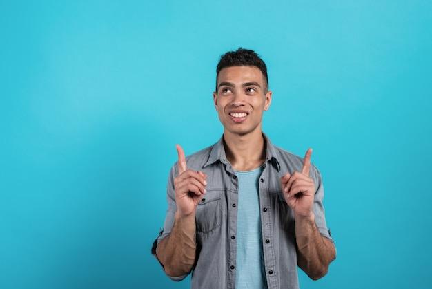 Recht junger mann zeigt geste mit den zeigefingerpunkten nach oben