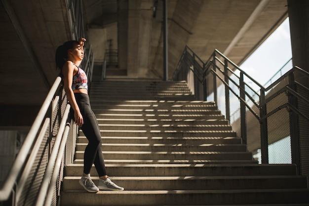 Recht junger weiblicher läufer, der auf treppen stillsteht