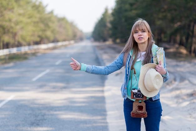 Recht junger weiblicher tourist, der entlang einer straße per anhalter fährt