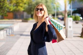 Recht junges Jugendlichmädchen, das viele Einkaufstaschen hält
