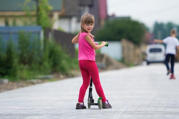 Recht junges langhaariges blondes kindermädchen in der rosa kleidung mit roller
