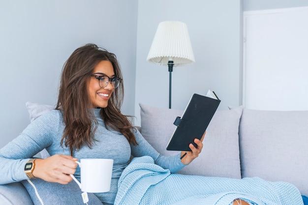 Recht junges mädchen, das auf sofa, trinkendem tee und lesebuch sitzt. gemütliche häusliche atmosphäre