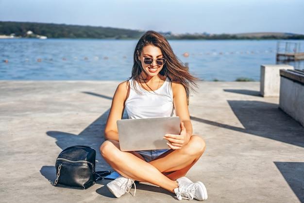 Recht junges mädchen, das den laptop im freien im stadtpark verwendet.