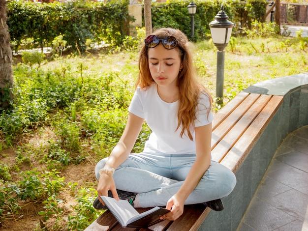 Recht junges mädchen, das ein buch auf einer bank in einem park liest