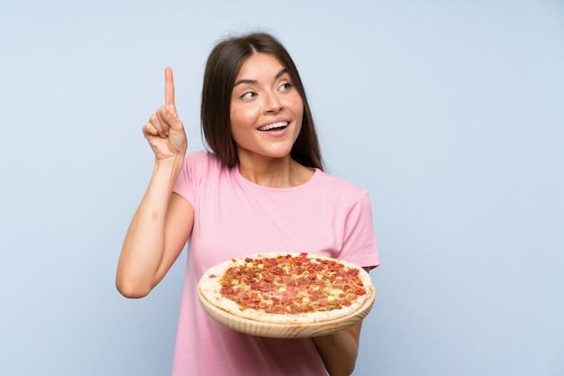 Recht junges mädchen, das eine pizza über der lokalisierten blauen wand beabsichtigt, die lösung beim anheben eines fingers zu verwirklichen hält