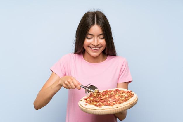 Recht junges mädchen, das eine pizza über getrennter blauer wand anhält