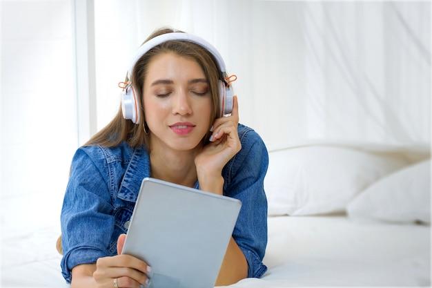 Recht junges mädchen hört die musik von der tablette auf dem weißen bett