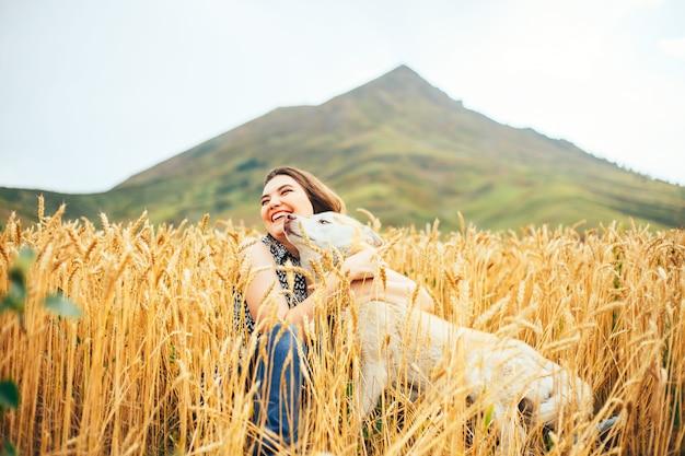 Recht junges mädchen mit dem brunettehaar und ihrem yorkshire-terrier an einem sommertag